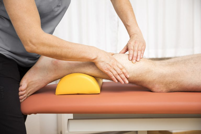 A person receiving a remedial massage for their legs